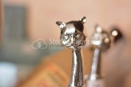 Close view of a silver cat head decorative object.