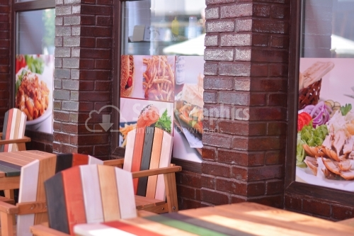 Colored wooden chairs and tables. Terrace of a fast food restaurant.