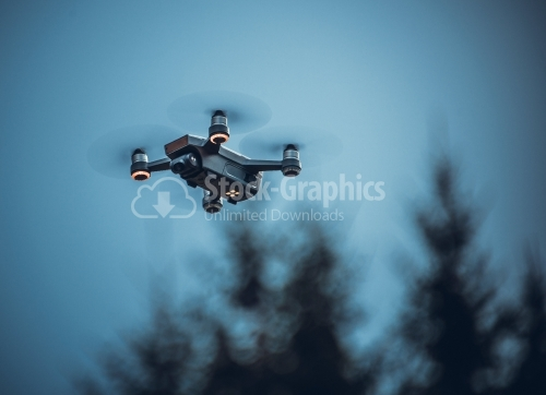 Drone with digital camera, hovering in blue sky