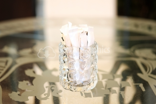 Thick glass cup filled with sugar sachets.