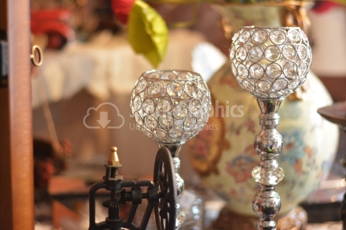 Two candlesticks with precious stones on the shelf of a shop.