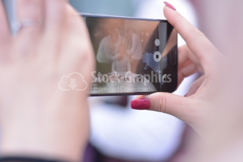 Young lady taking photos with her phone.